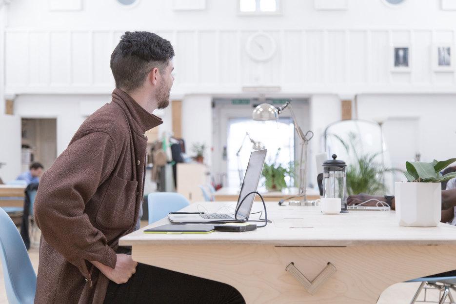 Man sits behind an Opendesk Team Desk inside Maker Wharf