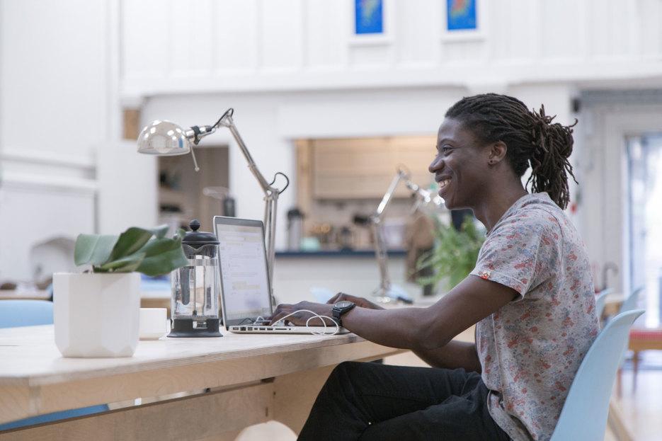 Man uses laptop at an Opendesk Team Desk inside Maker Wharf